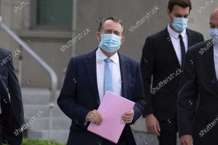 Candidate for Director General of the World Trade Organization (WTO), British Liam Fox (C) wears a protective mask as a precaution against the spread COVID-19, as he arrives for the WTO Director-General selection process, at the headquarters of the World Trade Organization (WTO) in Geneva, Switzerland, 17 July 2020.