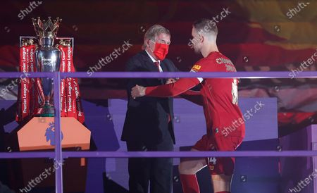 Stock Image of Jordan Henderson of Liverpool receives the trophy from Sir Kenny Dalglish