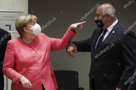 German Chancellor Angela Merkel, left, speaks with Bulgaria's Prime Minister Boyko Borissov during a round table meeting at an EU summit in Brussels, . Leaders from 27 European Union nations meet face-to-face on Friday for the first time since February, despite the dangers of the coronavirus pandemic, to assess an overall budget and recovery package spread over seven years estimated at some 1.75 trillion to 1.85 trillion euros