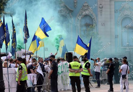 Ukrainian flags are seen through smoke over demonstrators during the Hands Off Language! Day 2. The Bonfire protest action against draft law N2362 'On Amendments to Certain Legislative Acts of Ukraine on Teaching in the State Language in Academic Institutions' outside the Verkhovna Rada building, Kyiv, capital of Ukraine.