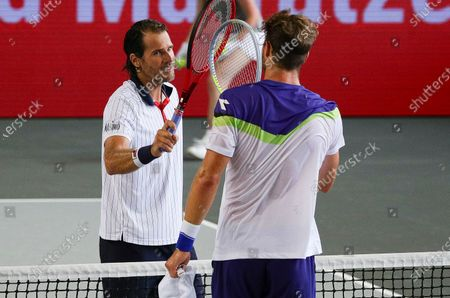 Stock Image of Tommy Haas of Germany (L) and Jan-Lennard Struff of Germany  bump rackets at the end of their match of the second stage of the bett1ACES tennis tournament held at hanger 6 of the inactive Tempelhofer feld airport, in Berlin, Germany, 17 July, 2020. The second part of the exhibition tournament will be played on a hard surface, in an airport hanger converted to a small tennis stadium and will be held under strict hygiene restrictions made to cope with the spread of the coronavirus SARS-CoV-2 which causes the COVID-19 disease.
