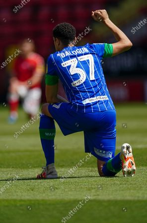 Leon Balogun of Wigan Athletic takes a knee in support of the Black Lives Matter movement prior to kick-off