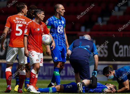Sam Sayed Morsy of Wigan Athletic receives medical treatment on the pitch by medical staff wearing full personal protective equipment (PPE)