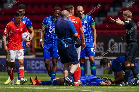 The referee instructs Kal Naismith of Wigan Athletic and Jamal Lowe of Wigan Athletic to step back as Sam Sayed Morsy of Wigan Athletic receives medical treatment on the pitch by medical staff wearing full personal protective equipment (PPE)