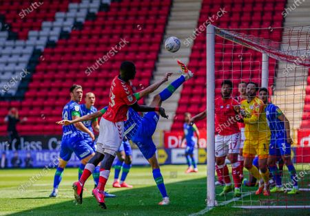 Leon Balogun of Wigan Athletic attempts to clear the ball to deny Naby Sarr of Charlton Athletic