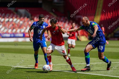 Jake Forster-Caskey of Charlton Athletic is challenged by Kal Naismith of Wigan Athletic and Sam Sayed Morsy of Wigan Athletic