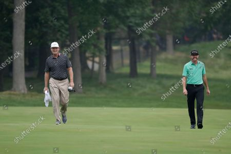 Ernie Els, of South Africa, left, and Jimmy Walker smile as they walk on the 13th fairway during the second round of the Memorial golf tournament, in Dublin, Ohio