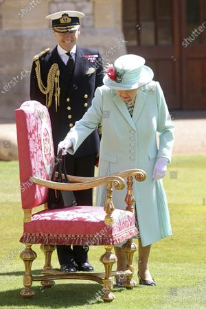 Britain's Queen Elizabeth places her handbag on a chair before awarding Captain Sir Thomas Moore his knighthood during a ceremony at Windsor Castle in Windsor, England, . Captain Sir Tom raised almost £33 million for health service charities by walking laps of his Bedfordshire garden