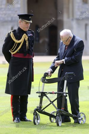 Captain Sir Thomas Moore arrives to receive his knighthood from Britain's Queen Elizabeth, during a ceremony at Windsor Castle in Windsor, England, . Captain Sir Tom raised almost £33 million for health service charities by walking laps of his Bedfordshire garden