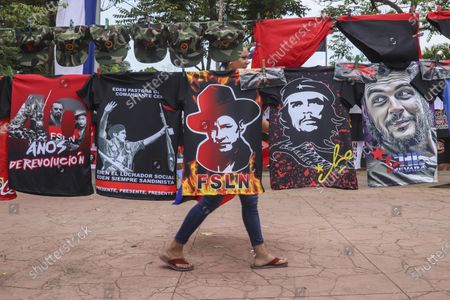 """Woman walks past T-shirts for sale promoting The Sandinista National Liberation Front ruling party on the sidelines of a new monument, called the Peace Bell, before its inauguration ceremony later in the day in Managua, Nicaragua, . Nicaraguan President Daniel Ortega's government is being deterred by the new coronavirus from holding the usual mass celebration to mark the victory of the country's revolution July 19, and will instead unveil a new addition to its collection of monuments. At right are two T-shirts of Cuba's revolutionary hero Ernesto """"Che"""" Guevara"""
