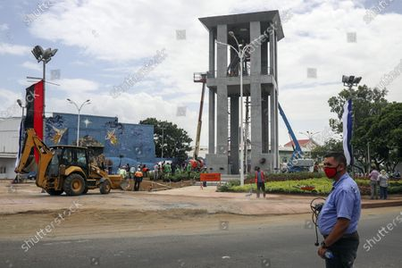 Workers ready a new monument, called the Peace Bell, before its inauguration ceremony later in the day in Managua, Nicaragua, . Nicaraguan President Daniel Ortega's government is being deterred by the new coronavirus from holding the usual mass celebration to mark the victory of the country's revolution July 19, so will instead unveil a new addition to its collection of monuments