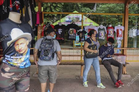 People wait at a bus stop where a vendor sells T-shirts promoting Nicaraguan President Daniel Ortega and the ruling political party of the Sandinista National Liberation Front, before an event commemorating the uprising that overthrew the Anastasio Somoza family in Managua, Nicaragua