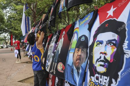 """Vendor sells T-shirts promoting Nicaraguan President Daniel Ortega and The Sandinista National Liberation Front ruling party on the sidelines of a new monument, called the Peace Bell, before its inauguration ceremony later in the day in Managua, Nicaragua, . Nicaraguan President Daniel Ortega's government is being deterred by the new coronavirus from holding the usual mass celebration to mark the victory of the country's revolution July 19, and will instead unveil a new addition to its collection of monuments. At right is a T-shirt of Cuba's revolutionary hero Ernesto """"Che"""" Guevara"""