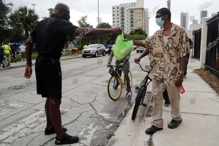 Miami Heat executive Alonzo Mourning, left, passes out hot meals during a food distribution sponsored by the Miami Dolphins NFL football team at the Overtown Youth Center during the coronavirus pandemic, in the Overtown neighborhood of Miami