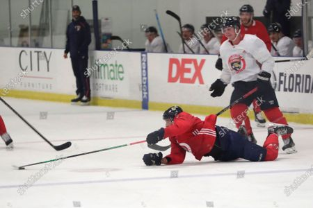 Florida Panthers' Aaron Ekblad, left, falls to the ice as Noel Acciari looks on during NHL hockey practice, in Coral Springs, Fla