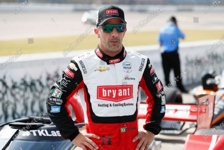 Tony Kanaan, of Brazil, stands next to his car during qualifying for an IndyCar Series auto race, at Iowa Speedway in Newton, Iowa