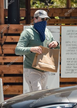 Jon Hamm is seen picking up take-out food