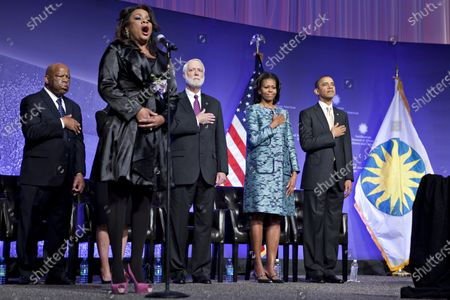 United States President Barack Obama and First Lady Michelle Obama listen to the National Anthem sung by Denyce Graves at the groundbreaking ceremony of the Smithsonian National Museum of African American History and Culture in Washington, D.C.. The museum is scheduled to open in 2015 and will be the only national museum devoted exclusively to the documentation of African American life, art, history and culture. From left to right: U.S. Representative John Lewis (Democrat of Georgia); Denyce Graves; Wayne Clough, Secretary, Smithsonian Institution; Mrs. Obama; and President Obama..