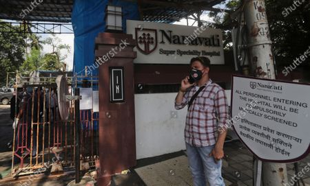 Stock Image of Man speaks on a phone outside Nanavati hospital, where Bollywood legend Amitabh Bachchan, his son Abhishek Bachchan, daughter-in-law Aishwarya Rai Bachchan and granddaughter are being treated for COVID-19, in Mumbai, India