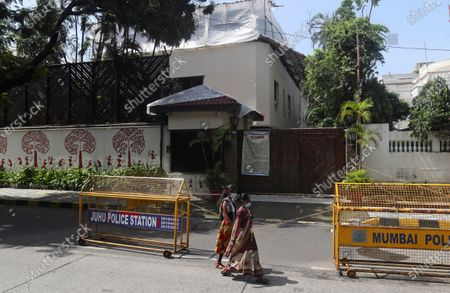 Women wearing mask walk past the house of Bollywood superstar Amitabh Bachchan in Mumbai, India, . Bachchan, his son Abhishek Bachchan, daughter-in-law Aishwarya Rai Bachchan and granddaughter are being treated for COVID-19 at a hospital in the city