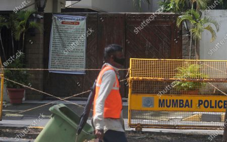 Municipal worker walks past the house of Bollywood superstar Amitabh Bachchan in Mumbai, India, . Bachchan, his son Abhishek Bachchan, daughter-in-law Aishwarya Rai Bachchan and granddaughter are being treated for COVID-19 at a hospital in the city
