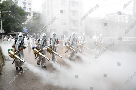 A rescue team disinfect the street in flood-hit Wuqiao subdistrict in Wanzhou District, southwest China's Chongqing Municipality, July 18, 2020. After a flood hit many streets along the Wuqiao River on Thursday, rescuers helped local residents clear debris.