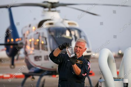 Stock Photo of Pilot Michael Bobeck at the start of his 12 hours night shift checks fuel of Mercy Air air ambulance helicopter based at Imperial County Airport, Imperial. Imperial County Airport on Sunday, July 12, 2020 in Imperial, CA. (Irfan Khan/Los Angeles Times)