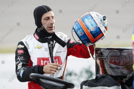 Tony Kanaan, of Brazil, puts on his helmet before the start of the IndyCar Series auto race, at Iowa Speedway in Newton, Iowa