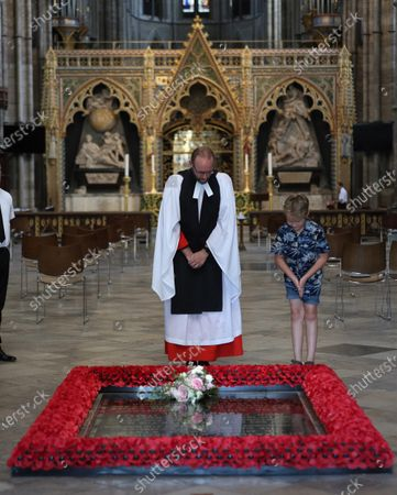 Stock Photo of Reverend Anthony Ball, Canon of Westminster in Westminster Abbey in London with Toby Wright, son of the Reverend Paul Wright, Sub-Dean of the Chapel Royal, who brought Princess Beatrice's wedding bouquet straight from the wedding in Windsor which, like those of Royal brides, is traditionally placed on the Tomb of the Unknown Warrior