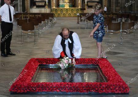 Reverend Anthony Ball, Canon of Westminster in Westminster Abbey in London with Toby Wright, son of the Reverend Paul Wright, Sub-Dean of the Chapel Royal, who brought Princess Beatrice's wedding bouquet straight from the wedding in Windsor which, like those of Royal brides, is traditionally placed on the Tomb of the Unknown Warrior