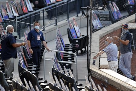 New York Yankees manager Aaron Boone, right, general manager Brian Cashman, second right, talks with New York Mets general manager Brodie Van Wagenen, second left, prior to their baseball teams spring training game, in New York
