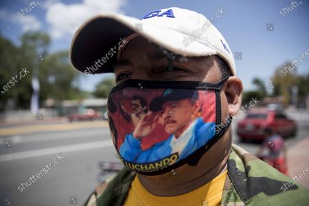 A man wears a face mask depicting Nicaraguan President Daniel Ortega in honor of the Nicaraguan revolution in Managua, Nicaragua, 18 July 2020. For the first time since 1979, the old center of Managua will not serve as the stage for the largest annual party of the Sandinistas, the Nicaraguan popular revolution, celebrated annually on 19 July, due to the coronavirus pandemic.