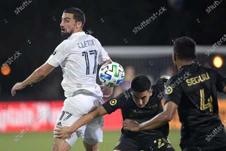 Galaxy midfielder Sebastian Lletget (17) competes for the ball with Los Angeles FC midfielder Eduard Atuesta (20) and defender Eddie Segura (4) during the first half of an MLS soccer match, in Kissimmee, Fla