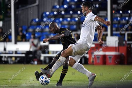 Los Angeles FC forward Bradley Wright-Phillips, back, scores a goal past LA Galaxy defender Giancarlo Gonzalez during the second half of an MLS soccer match, in Kissimmee, Fla