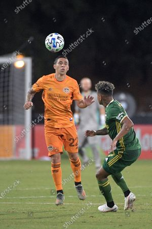 Houston Dynamo midfielder Matias Vera (22) wins a header in front of Portland Timbers forward Andy Polo (7) during the second half of an MLS soccer match, in Kissimmee, Fla