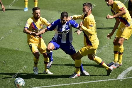 Alaves' Edgar Mendez, center, fights for the ball with Barcelona's Jordi Alba, left, and Clement Lenglet during the Spanish La Liga soccer match between Alaves and FC Barcelona, at Mendizorroza stadium, in Vitoria, northern Spain