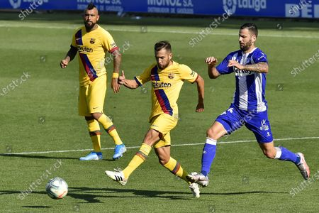 Barcelona's Jordi Alba, center, fights for the ball with Alaves' Luis Rioja during the Spanish La Liga soccer match between Alaves and FC Barcelona, at Mendizorroza stadium, in Vitoria, northern Spain