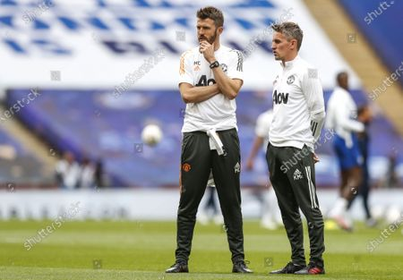 Manchester United's English first-team coach Michael Carrick (L) speaks with Manchester United's Northern Irish first-team coach Kieran McKenna prior to the English FA Cup semi final match between Manchester United and Chelsea FC at the Wembley stadium in London, Britain, 19 July 2020.