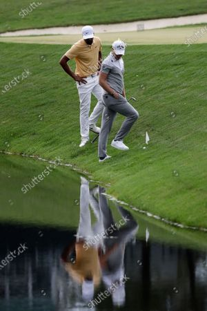 Tony Finau, left, and Danny Willet take drops after both hit into the water next to the 14th fairway during the final round of the Memorial golf tournament, in Dublin, Ohio