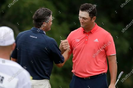 Jon Rahm, of Spain, right, is congratulated by Ryan Palmer after winning the Memorial golf tournament, in Dublin, Ohio