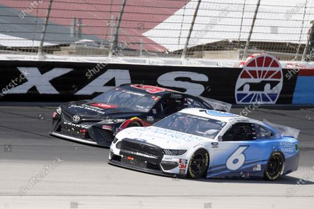 Daniel Suarez, left, and Ryan Newman, right, come out of Turn 4 during a NASCAR Cup Series auto race at Texas Motor Speedway in Fort Worth, Texas