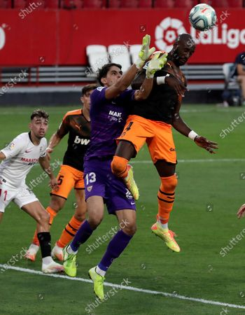 Sevilla's goalkeeper Yassine Bounou 'Bono' (C) vies for the ball with Valencia's Eliaquim Mangala (R) during the Spanish LaLiga soccer match between Sevilla FC and Valencia CF held at Sanchez Pizjuan Stadium, in Seville, Spain, 19 July 2020.