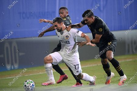 Galaxy midfielder Sebastian Lletget (17) competes with Los Angeles FC defender Diego Palacios, rear, and defender Eddie Segura, right, for a ball during the first half of an MLS soccer match, in Kissimmee, Fla