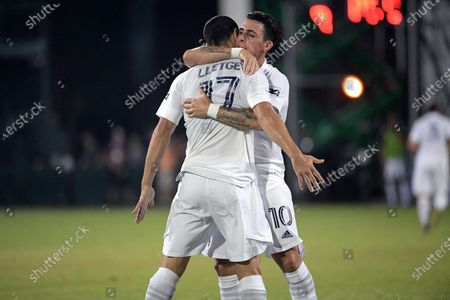 Galaxy forward Cristian Pavon (10) andmidfielder Sebastian Lletget (17) celebrate after Los Angeles FC forward Latif Blessing scored an own goal during the first half of an MLS soccer match, in Kissimmee, Fla