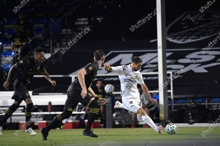 Galaxy midfielder Sebastian Lletget, right, kicks the ball in front of the Los Angeles FC midfielder Mark-Anthony Kaye, left, and defender Dejan Jakovic during the first half of an MLS soccer match, in Kissimmee, Fla