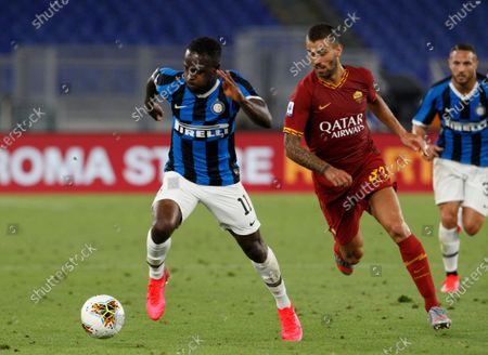 Inter Milan's Victor Moses, left, and Roma's Leonardo Spinazzola challenge for the ball during the Serie A soccer match between Roma and Inter Milan, at the Rome Olympic Stadium