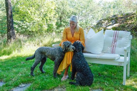 Stock Picture of Crown Princess Mette-Marit, the consort of Crown Prince Haakon (heir apparent to the Norwegian throne), poses for a portrait with the dogs Milly Kakao (L) and Muffins Krakebolle (R) during her family's summer vacation on the island of Dvergsoya, Kristiansand, southern Norway, 19 July 2020.