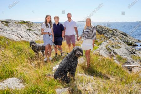 Crown Prince Haakon (2-R), the heir apparent to the Norwegian throne, poses for a portrait alongside his consort, Crown Princess Mette-Marit (R), and his children, Princess Ingrid Alexandra (L) and Prince Sverre Magnus (2-L), as well as the dogs Milly Kakao and Muffins Krakebolle, during the princely family's summer vacation on the island of Dvergsoya, Kristiansand, southern Norway, 19 July 2020.