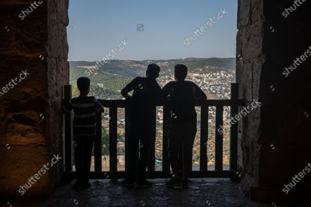 Domestic tourists enjoy the view from inside the Ajloun Castle - located about 80 kilometers (50 miles) to the northwest of the capital, Amman - in Ajloun, Jordan, 19 July 2020. This fortified castle was built on top of the remains of on an old monastery by a general who was part of the army of the famed Ayyubid ruler Sultan An-Nasir Salah ad-Din (a.k.a. Saladin) in the 12th century AD. According to various historical accounts, the castle/fort served as a control point in the route between Egypt and Damascus and was the main Muslim fortress of protection against the crusaders who launched the medieval campaigns to conquer the Holy Land. Jordan's tourism authorities have developed a digital app containing information and discounts for Jordanians and residents of the kingdom aiming to visit the country's historical and touristic sites, as international tourism has ground to a halt following the global pandemic of the COVD-19 disease caused by the SARS-CoV-2 coronavirus and the subsequent closure of the Hashemite kingdom's airports to visitors from abroad.