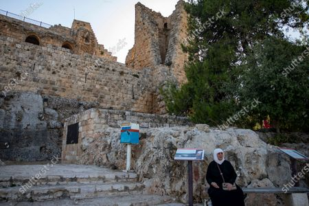 A woman sits on a wooden bench outside of the Ajloun Castle - located about 80 kilometers (50 miles) to the northwest of the capital, Amman - in Ajloun, Jordan, 19 July 2020. This fortified castle was built on top of the remains of on an old monastery by a general who was part of the army of the famed Ayyubid ruler Sultan An-Nasir Salah ad-Din (a.k.a. Saladin) in the 12th century AD. According to various historical accounts, the castle/fort served as a control point in the route between Egypt and Damascus and was the main Muslim fortress of protection against the crusaders who launched the medieval campaigns to conquer the Holy Land. Jordan's tourism authorities have developed a digital app containing information and discounts for Jordanians and residents of the kingdom aiming to visit the country's historical and touristic sites, as international tourism has ground to a halt following the global pandemic of the COVD-19 disease caused by the SARS-CoV-2 coronavirus and the subsequent closure of the Hashemite kingdom's airports to visitors from abroad.